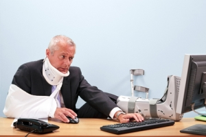 Injured businessman working at his desk